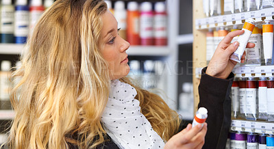 Buy stock photo Shot of a young female artist chooses tubes of paint in an art supplies store