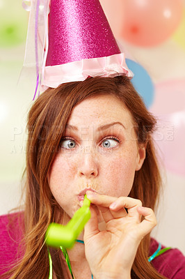 Buy stock photo Portrait of an attractive young woman pulling a silly face while blowing a party blower