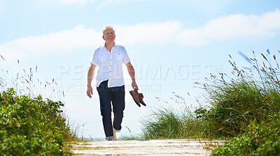 Buy stock photo A senior man walking through a park with his shoes in hand
