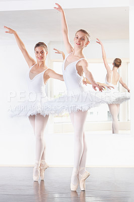 Buy stock photo Full length shot of two ballerinas practicing in a studio with a mirror behind them