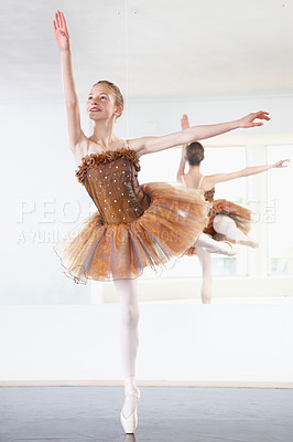 Buy stock photo Shot of a young ballerina rehearsing in a studio with a mirror behind her