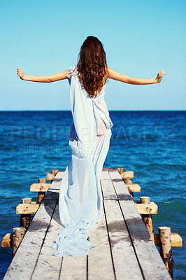 Buy stock photo Rear view of a young woman walking on the pier