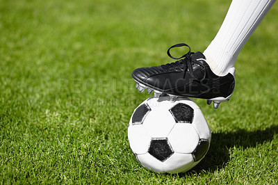 Buy stock photo Cropped shot of a female football players leg standing on a soccer ball