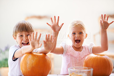 Buy stock photo Portrait of a little boy and girl looking excited while hollowing out their jack-o-lantern