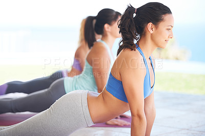 Buy stock photo Pilates instructor leading a class in stretching