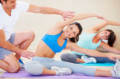 Buy stock photo Young woman doing a pilates class with the help of an instructor