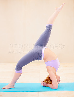 Buy stock photo Flexible woman in a yoga position while doing yoga by herself
