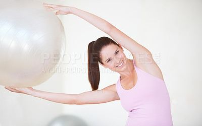 Buy stock photo Shot of an attractive young woman with her arms stretched above her head holding an exercise ball