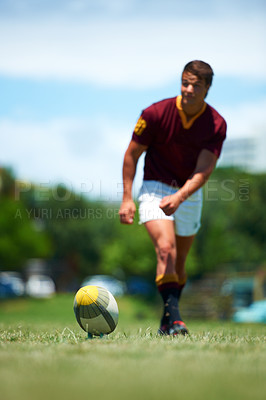Buy stock photo Full length shot of a young rugby player kicking for poles