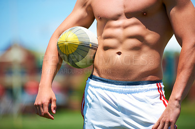 Buy stock photo Cropped shot of a shirtless young rugby player standing with the ball tucked under his arm