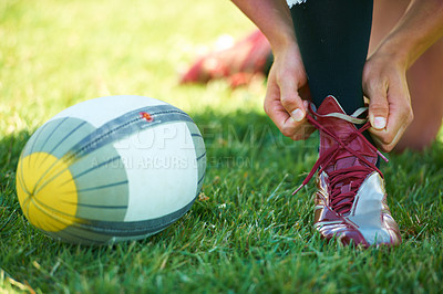 Buy stock photo Closeup shot of a rugby player tying his laces alongside a ball