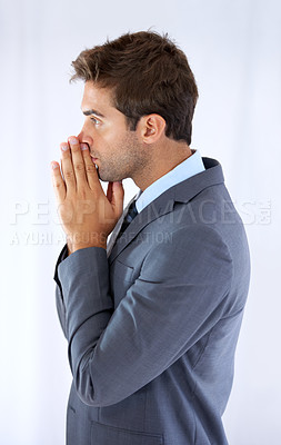 Buy stock photo Profile of a handsome young businessman standing with palms together rested against his mouth