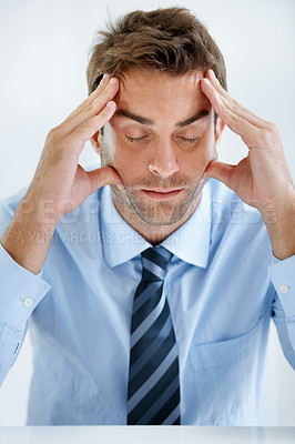 Buy stock photo A businessman sitting with hands holding his head and eyes closed