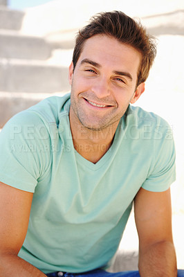 Buy stock photo Portrait of a handsome young man smiling while seated on a flight of stairs