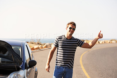 Buy stock photo A handsome young man standing on the side of the road besides his broken-down car and hitching a ride