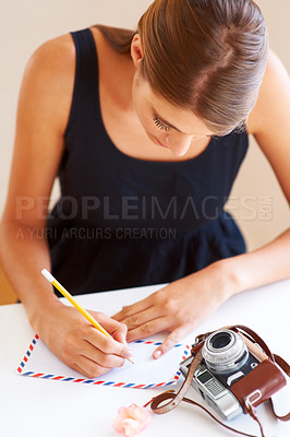 Buy stock photo A young woman writing an address on an envelope with a camera lying on her desk