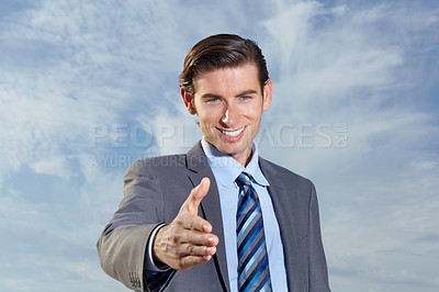 Buy stock photo A young businessman offering you a handshake against a bright sky