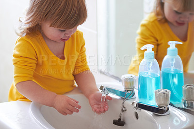Buy stock photo An adorable little girl washing her hands in the bathroom