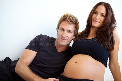 Buy stock photo Young expecting couple sitting together against a white background