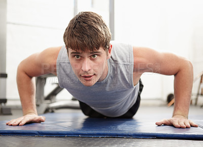 Buy stock photo Young man doing push ups on a mat in a gym