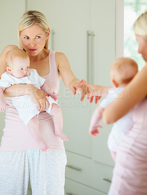 Buy stock photo A lovely mother pointing at the reflection in the mirror while holding her baby girl