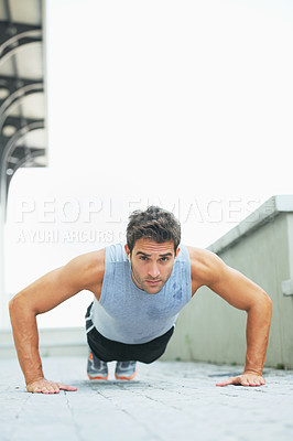 Buy stock photo Handsome young man doing push-ups - copyspace