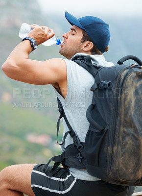 Buy stock photo Young hiker sitting and taking a sip from his water bottle