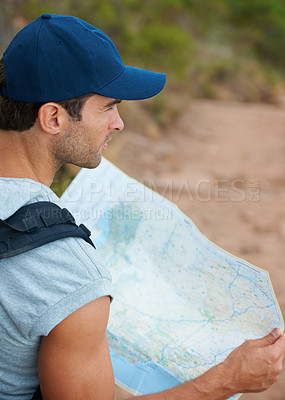 Buy stock photo Young male hiker holding a map - copyspace