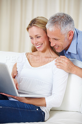 Buy stock photo A happy married couple working on their laptop at home