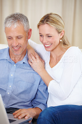 Buy stock photo A married couple sitting together with their laptop on the sofa