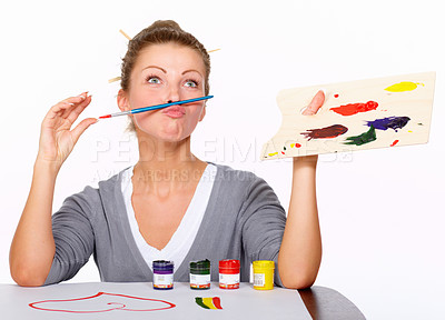 Buy stock photo Studio shot of an attractive woman balancing a paint brush on her upper lip
