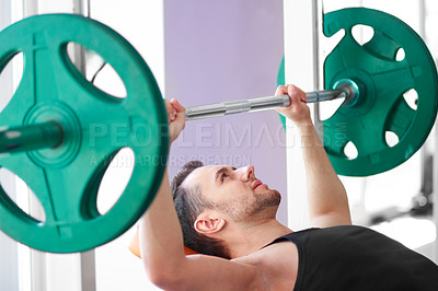 Buy stock photo Cropped shot of a man working out with weights in the gym