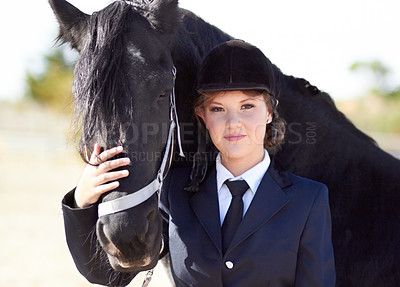 Buy stock photo Portrait of a young female rider stroking her horses face and smiling proudly at the camera