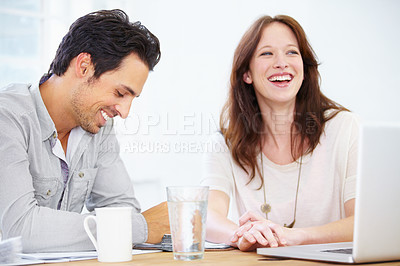 Buy stock photo Shot of a two positive-looking young design professionals sitting together and discussing something on a laptop