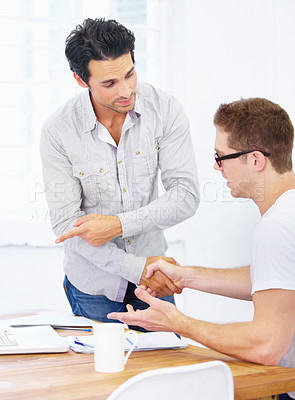 Buy stock photo Shot of a young designer sitting at his desk being congratulated by his manager