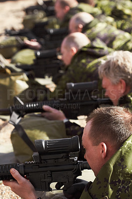 Buy stock photo A line of soldiers lying and aiming with their guns