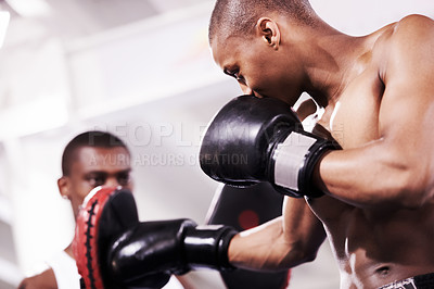 Buy stock photo A boxer practicing with his sparring partner in the ring