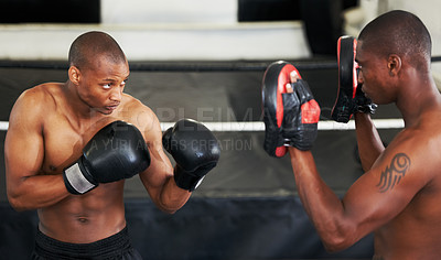 Buy stock photo A focused young boxer sparring with his partner in protective gloves