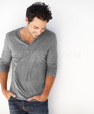 Buy stock photo A handsome young standing against a wall with his hands in his pockets