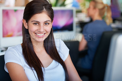 Buy stock photo Cropped shot of a young businesswoman working in the office with her colleague in the background