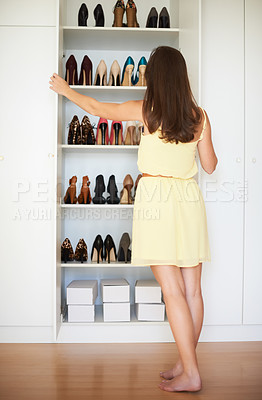 Buy stock photo Rearview of a woman looking into her closet for a pair of shoes