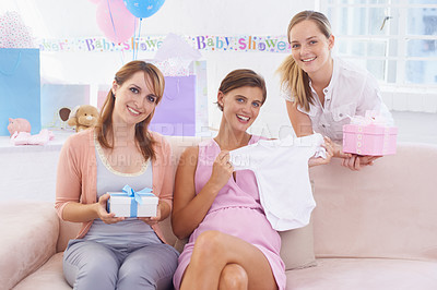 Buy stock photo A young pregnant woman receiving gifts from her pretty friends at her babyshower