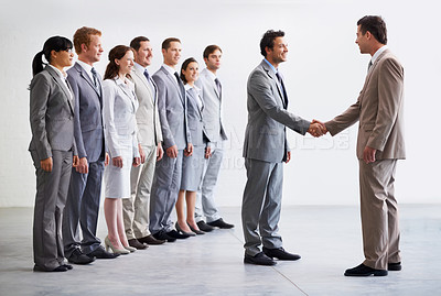 Buy stock photo A young businessman welcoming a new employee to the company as colleagues look on