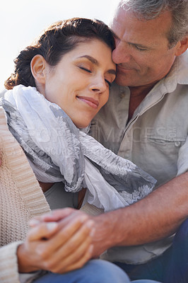 Buy stock photo A loving couple hugging each other affectionately outdoors