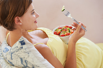 Buy stock photo A young pregnant woman enjoying a healthy salad while relaxing on the couch