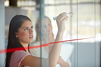 Buy stock photo A young businesswoman writing down plans on a glass pane