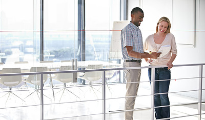 Buy stock photo Two business colleagues talking while looking over some paperwork