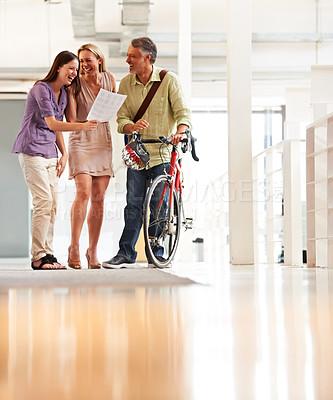 Buy stock photo Full length shot of a handsome bike messenger in an office