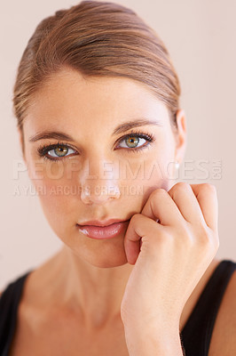 Buy stock photo Studio portrait of an attractive young woman with her hand on her chin and smiling at the camera
