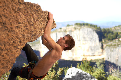 Buy stock photo Profile of a bare chested rock climber dangling off the edge of a cliff with mountains in the background